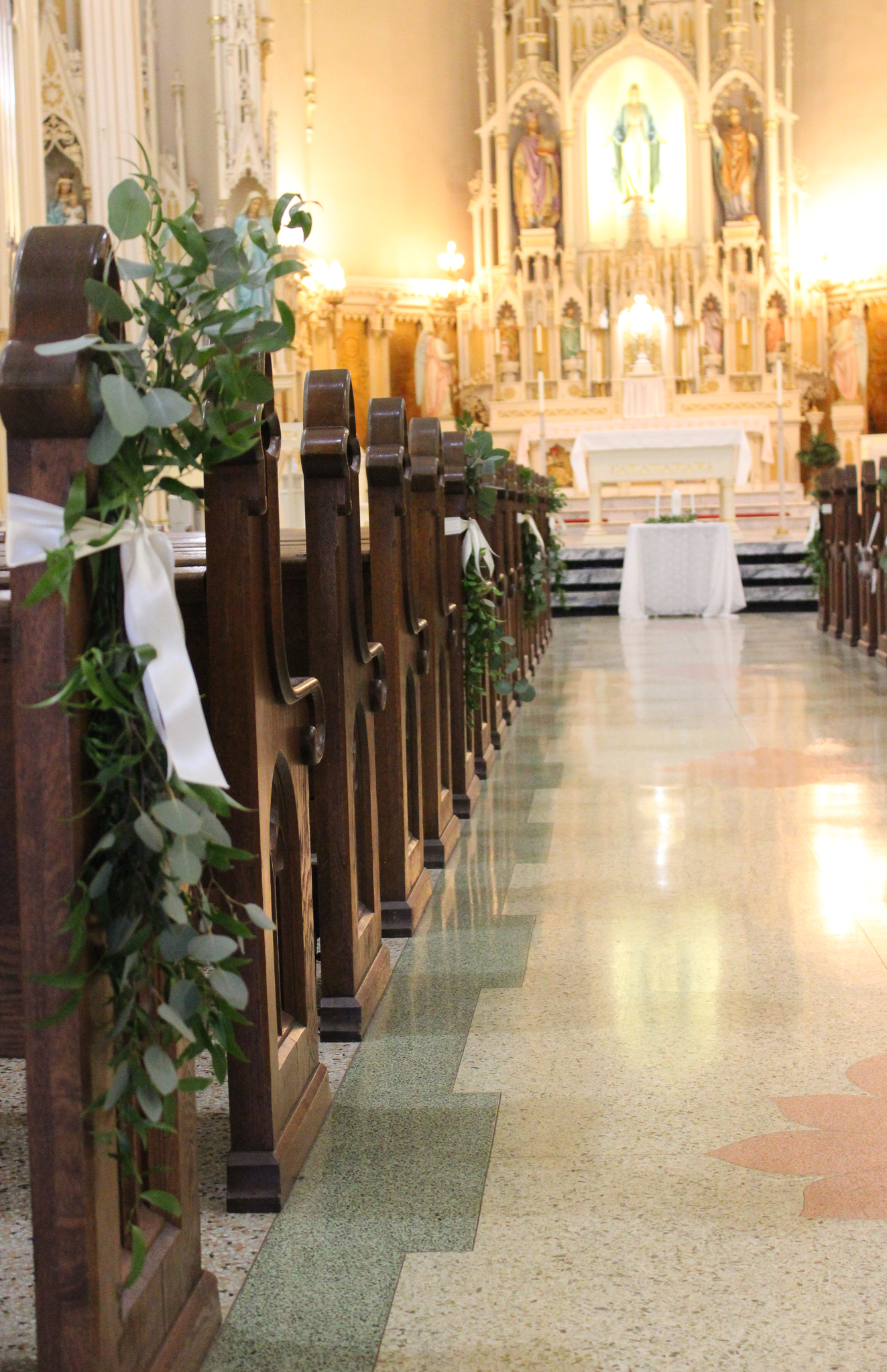 greenery swags tied with ribbon on end of pew
