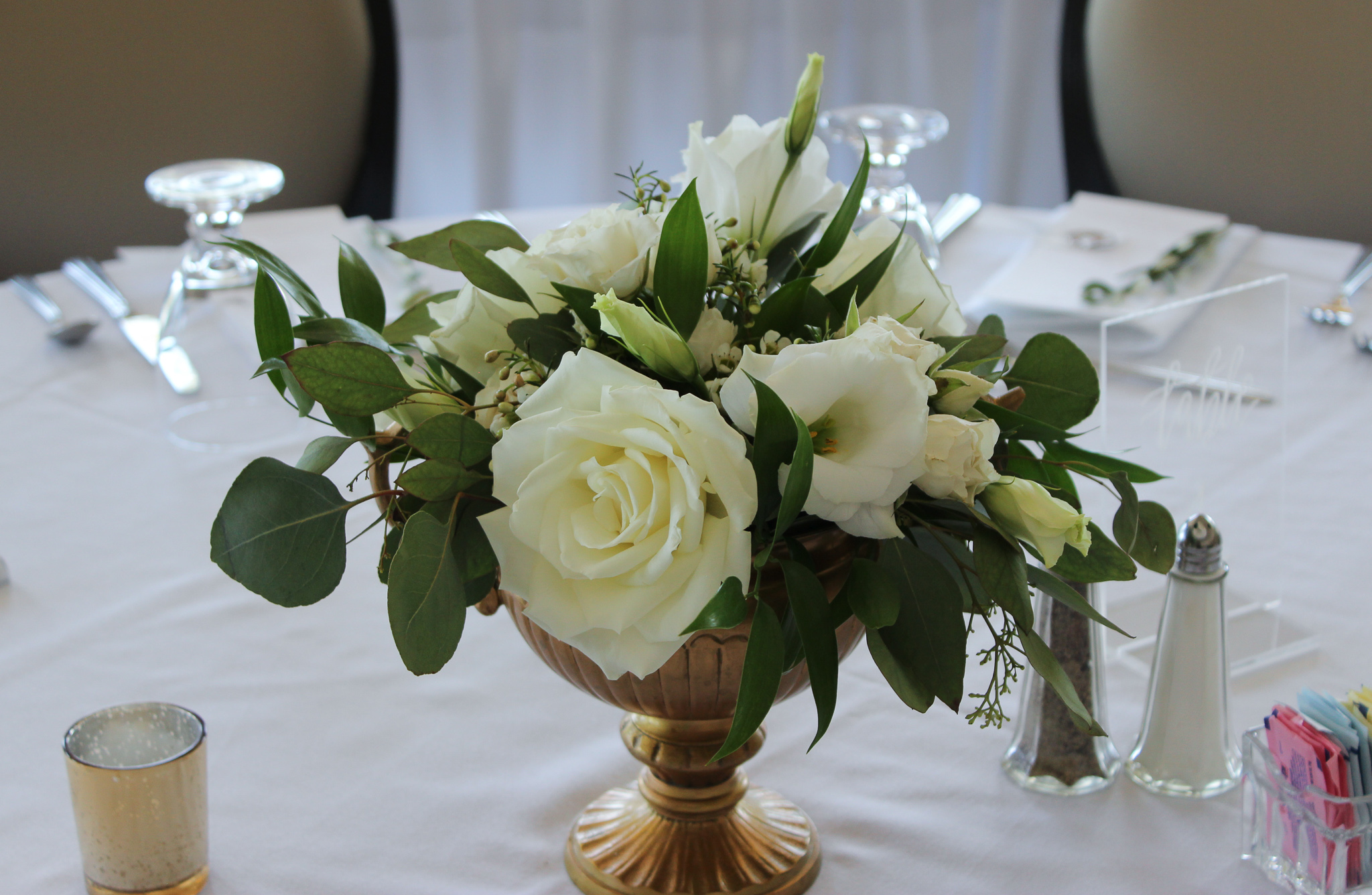 table centerpiece with white flowers in a gold compote