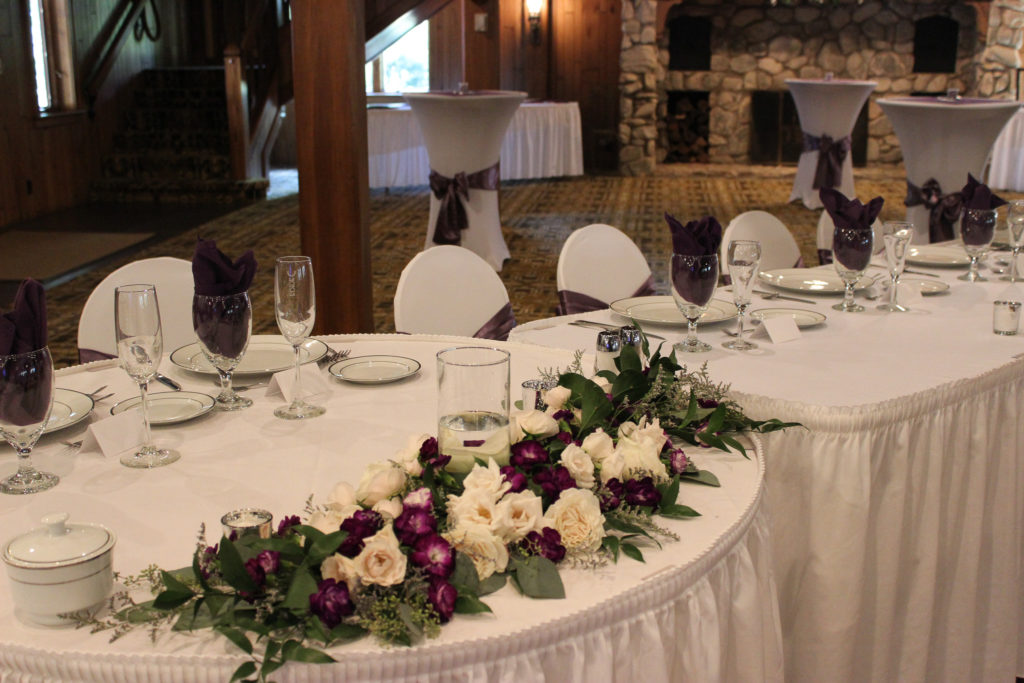 sweetheart table with purple and white floral garland