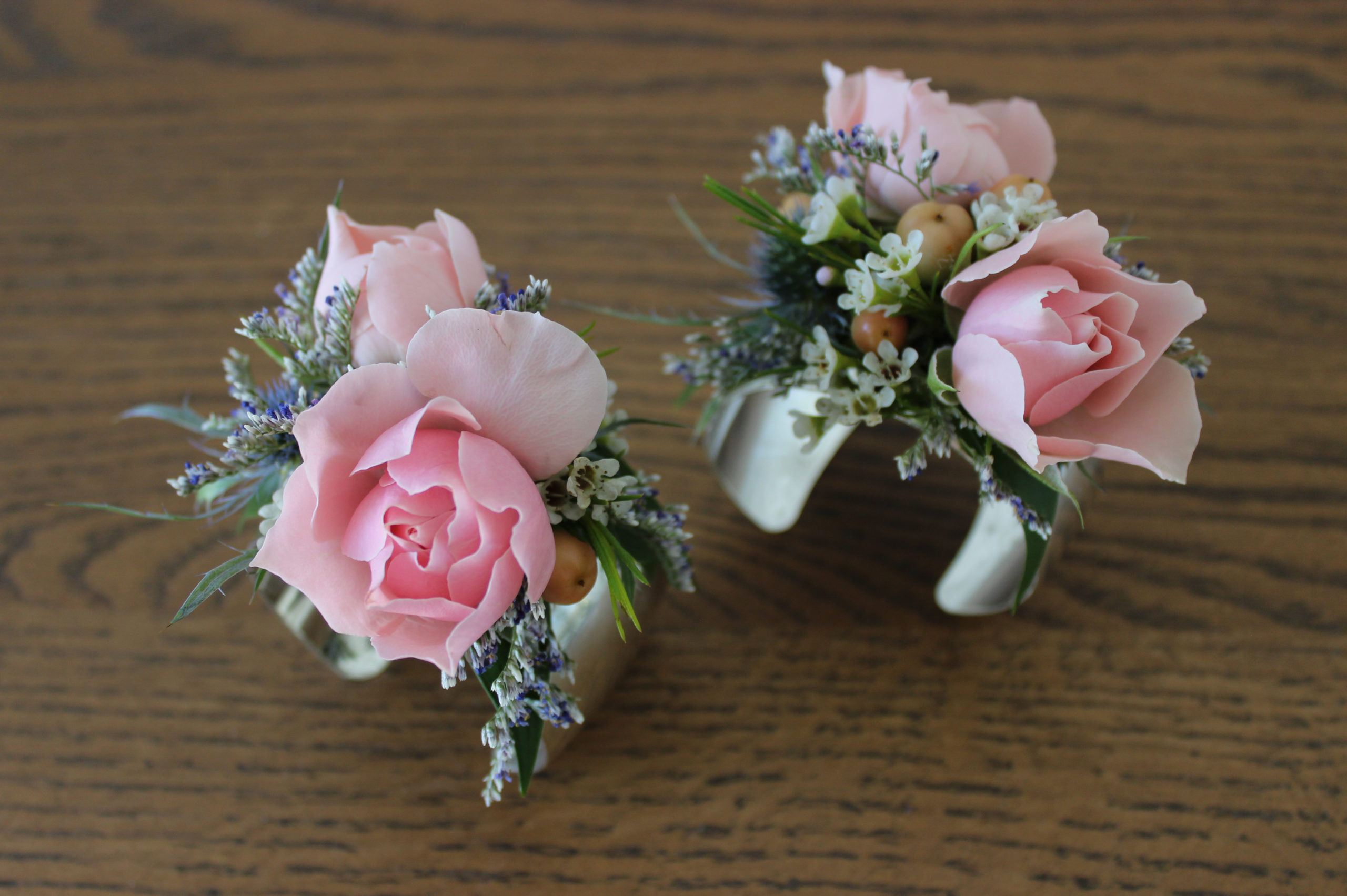 wrist corsages created with pink spray roses, peach hypericum berries, white wax flower, and lavender caspia on a silver cuff bracelet by evansville florist emerald design