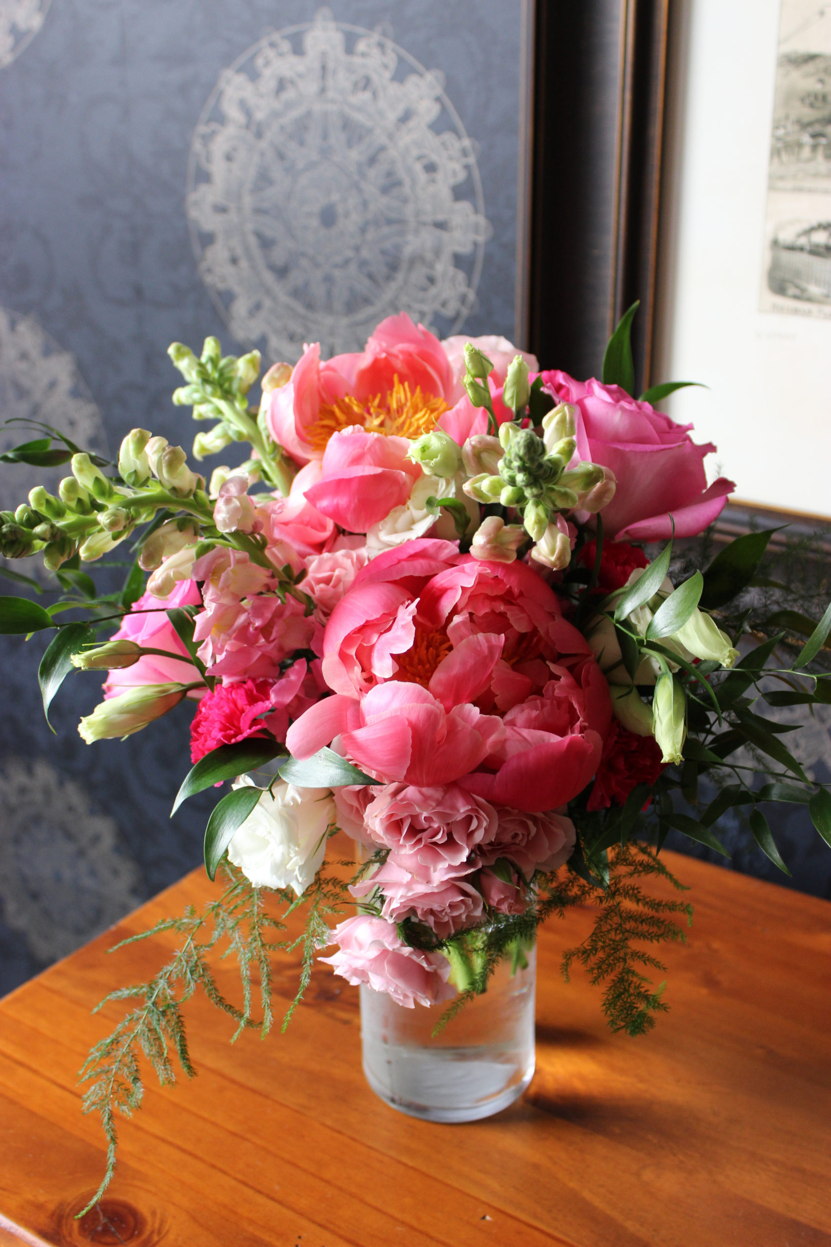 bridal bouquet created by evansville florist with coral peonies and supporting pink flowers