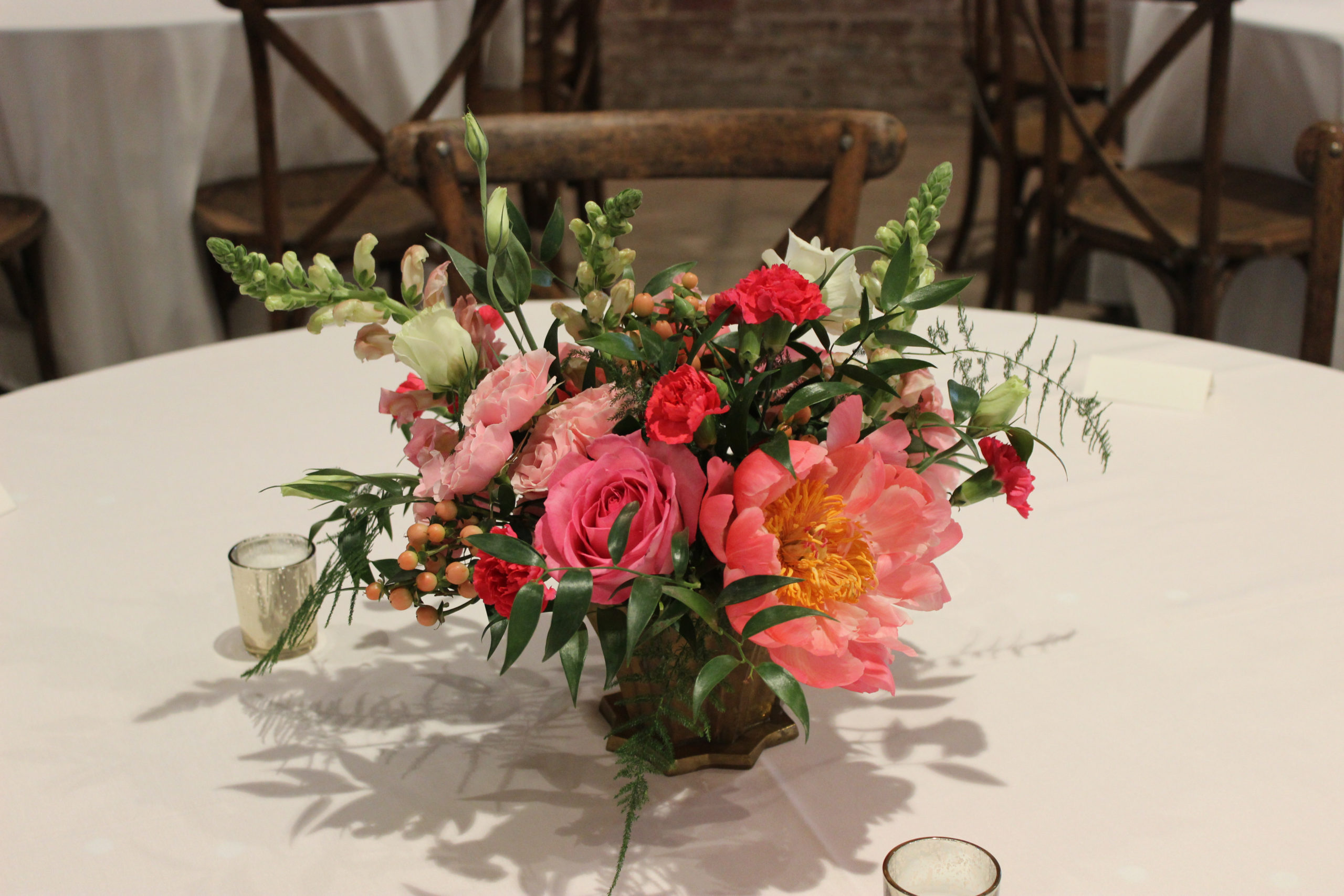 pink, coral, and peach flowers in a vintage gold container created by emerald design for a wedding at city view in downtown evansville