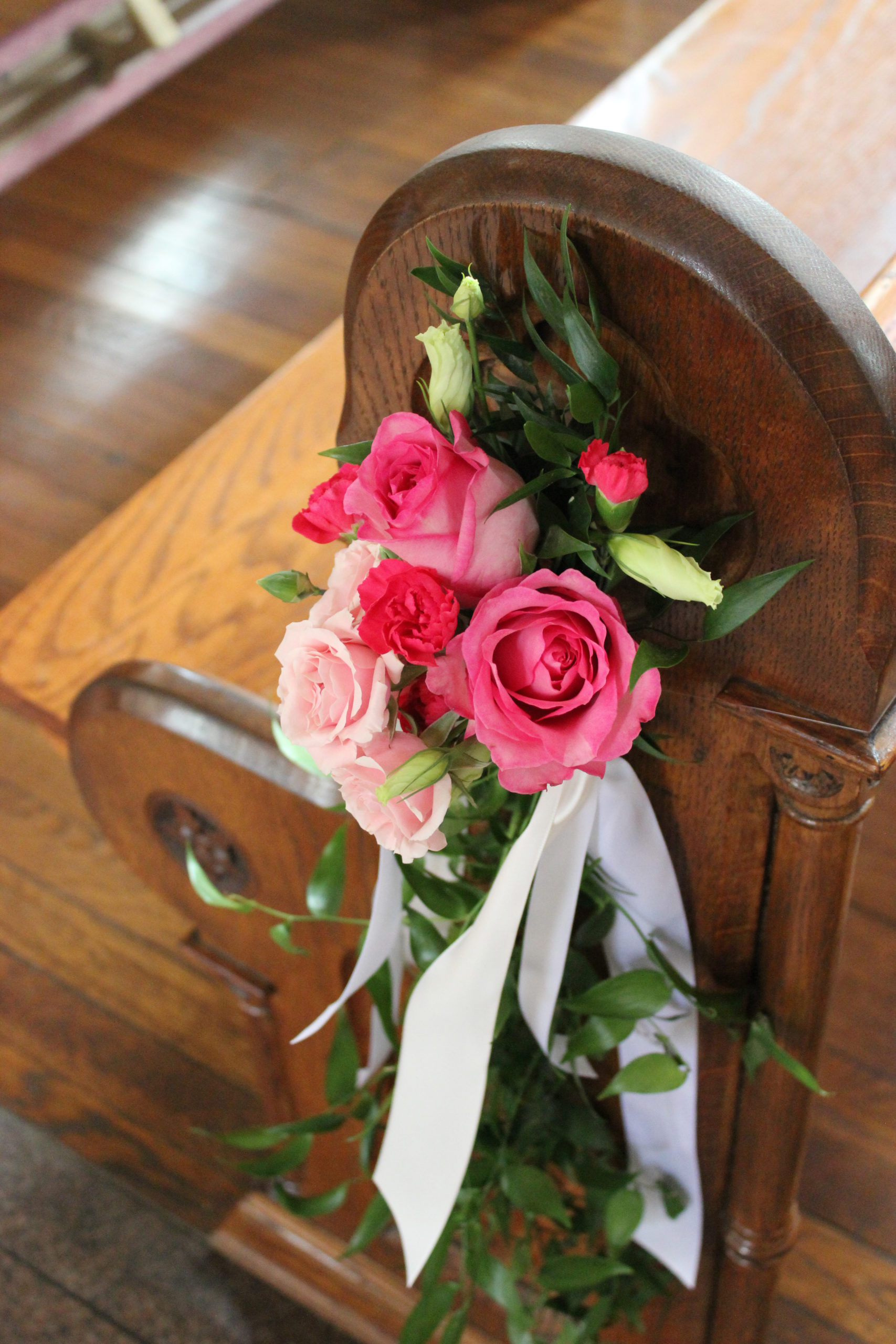 pink flowers added to pews for a wedding at St. Anthony Catholic Church