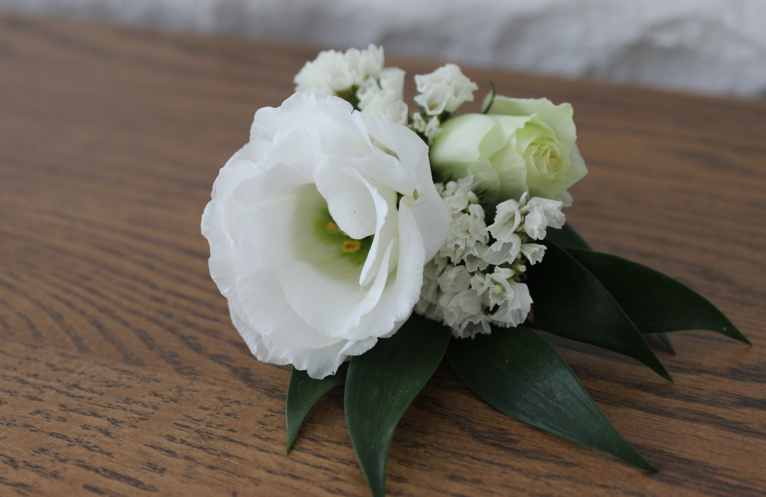 White lisianthus and statice boutonniere created by evansville indiana florist emerald design