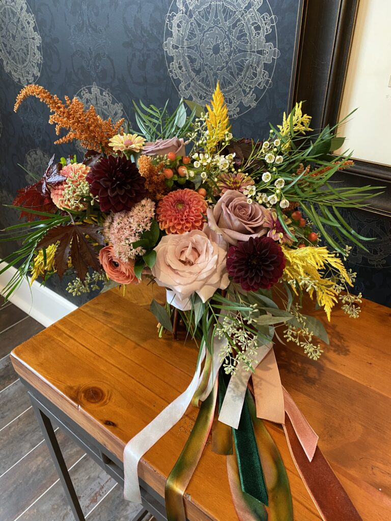 bridal bouquet created by evansville florist emerald design for a september wedding at City View at Sterling Square with burgundy, mauve, blush, and yellow tones