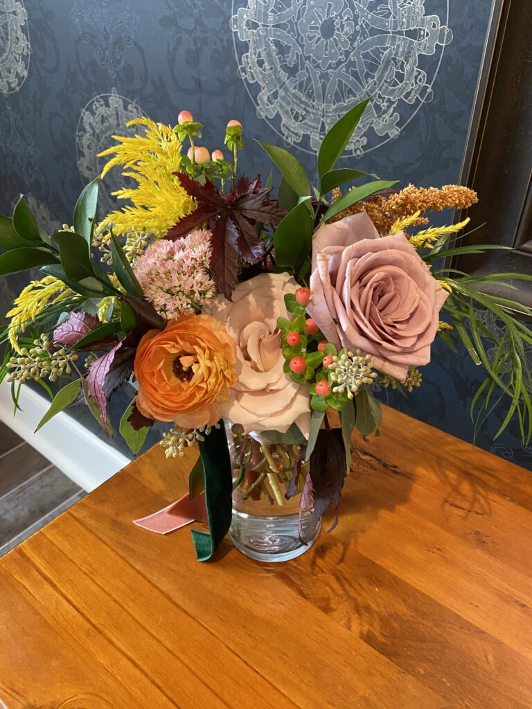 bridesmaid bouquet created by evansville florist emerald design for a september wedding at City View at Sterling Square with burgundy, mauve, blush, and yellow tones