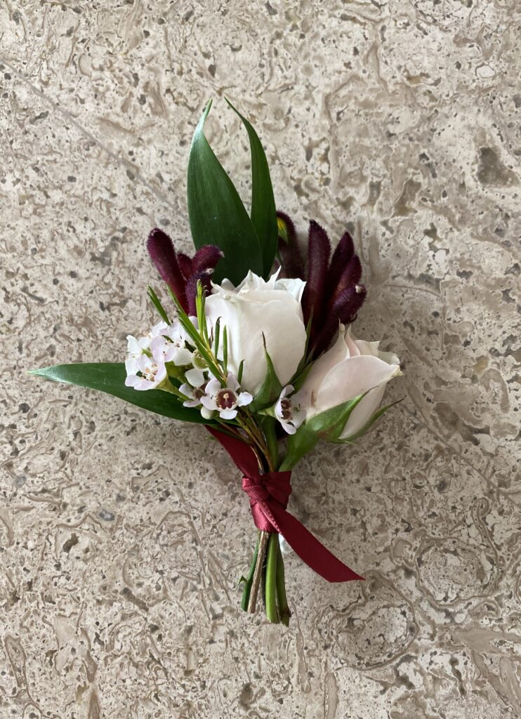 blush and burgundy boutonniere created by evansville florist emerald design