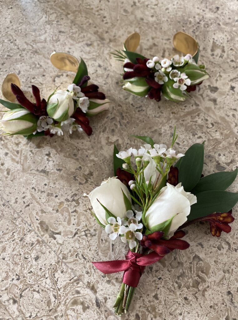 blush and burgundy corsages created by evansville florist emerald design