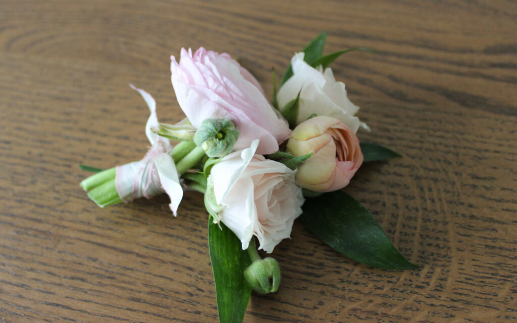Boutonniere in a pastel palette for a spring wedding, designed by evansville florist emerald design
