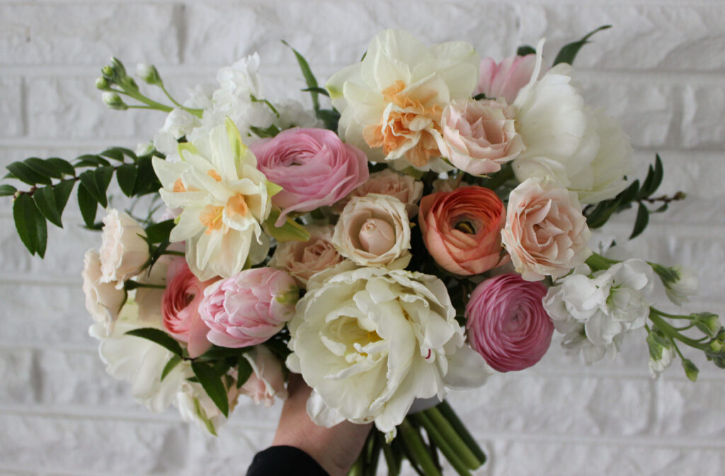 spring bridal bouquet featuring tulips, ranunculus, daffodils, and spray roses for a wedding in Newburgh Indiana